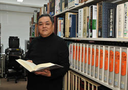 国際文化学部資料室にて。江村教授も制作に携わった手元の『世界の文字大辞典』は古代文字もイラスト化し世界中の文字を歴史的・体系的に解説した一冊